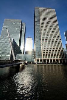 Tiro vertical de altos edificios de cuña cerca de un puente sobre el agua en un día soleado