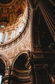 Tiro vertical de ángulo bajo de las hermosas pinturas y tallas en un edificio antiguo