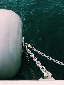 Tiro vertical de cadenas de metal conectadas a un barril a un lado del bote