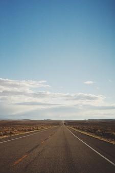 Tiro vertical de una carretera vacía en medio de un desierto bajo un hermoso cielo azul