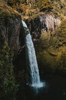 Tiro vertical de la cascada y el lago por los acantilados cubiertos de hierba