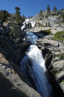 Tiro vertical de una cascada que fluye hacia abajo en los acantilados cerca del lago tahoe, ca con cielo azul y árboles