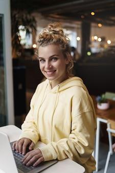 Tiro vertical de una chica atractiva sonriente que trabaja con un portátil en un café.