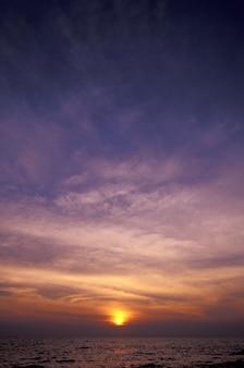 Tiro vertical de un cielo púrpura y amarillo sobre el mar al atardecer