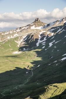 Tiro vertical de colinas cubiertas de hierba cerca de una montaña nevada con un cielo nublado