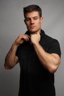 Tiro vertical de un collar de ajuste masculino sexy mientras está de pie contra una pared gris