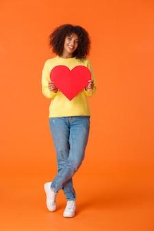 Tiro vertical de cuerpo entero hermosa, romántica y linda joven afroamericana con estilo y sosteniendo una gran tarjeta de corazón rojo para expresar amor, feliz día de san valentín, confesar simpatía.