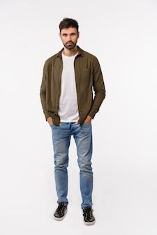 Tiro vertical de cuerpo entero hombre moderno descarado y confiado en abrigo, traje de jeans estilo callejero, tomados de las manos en los bolsillos, mirando asertivo, sonriente, preparándose una cita comercial, fondo blanco