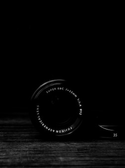 Tiro vertical en escala de grises de una lente de cámara sobre una superficie de madera