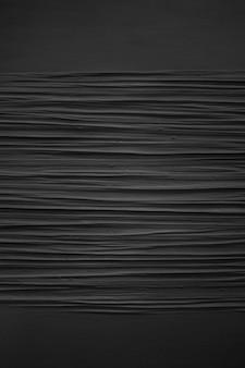 Tiro vertical en escala de grises de los patrones en una pared pintada de negro