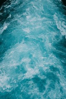 Tiro vertical de las espumosas olas de agua en el mar