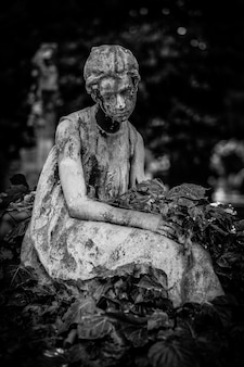 Tiro vertical de una estatua femenina rodeada de hojas en blanco y negro