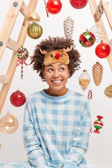 Tiro vertical de feliz soñadora mujer afroamericana tiene sueños de expresión pensativa sobre el milagro durante las vacaciones de invierno disfruta de un ambiente acogedor vestido con pijama contento de estar en casa. víspera de año nuevo