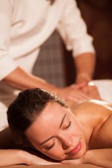 Tiro vertical de una hermosa mujer relajante en el centro de spa, recibir masaje de espalda. atractiva mujer disfrutando de una relajante terapia de masaje. masajista profesional trabajando. resort, hotel, recreación.