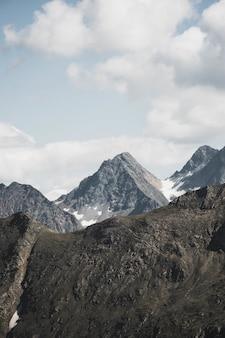 Tiro vertical de hermosas montañas nevadas bajo nubes impresionantes en cielo azul claro