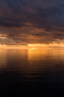 Tiro vertical de la impresionante puesta de sol en el cielo nublado sobre el océano