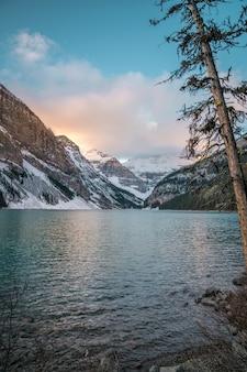 Tiro vertical de un lago en el centro de montañas nevadas y el cielo brillante en el fondo