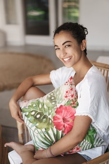 Tiro vertical linda mujer morena hispana en camiseta blanca, sentada con las piernas cruzadas en una cómoda silla de ratán