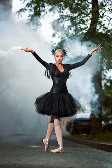 Tiro vertical de longitud completa de una hermosa bailarina de cabello rubio con corsé negro y tutú bailando en las calles de la ciudad humo en el fondo dramático desempeño épico expresivo.
