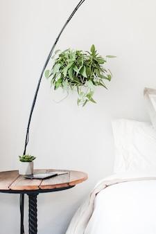 Tiro vertical de una mesa auxiliar redonda marrón junto a una cama