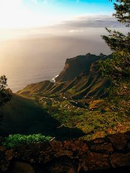 Tiro vertical de montaña verde y edificios en una colina en el medio cerca del mar en un día soleado
