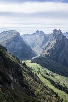 Tiro vertical de montañas boscosas bajo un cielo nublado durante el día