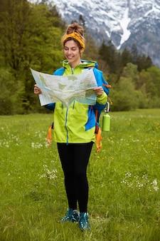 Tiro vertical de mujer alegre tiene viaje aventurero, navega en la naturaleza con mapa topográfico