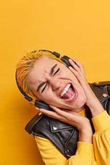 Tiro vertical de mujer hipster meloman con cabello teñido inclina la cabeza canta canción junto escucha música en auriculares inalámbricos usa atuendo de moda disfruta de lista de reproducción de rock aislada sobre pared amarilla