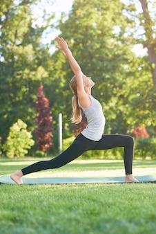 Tiro vertical de una mujer joven que hace yoga en el parque de pie en posición de guerrero deporte fitness armonía recreación mañana estacional deportivo.