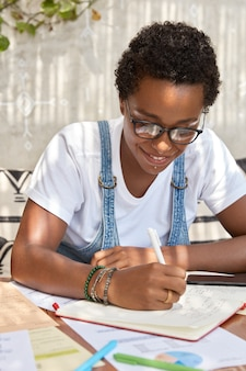 Tiro vertical de mujer negra tiene sonrisa tierna, pelo corto y rizado