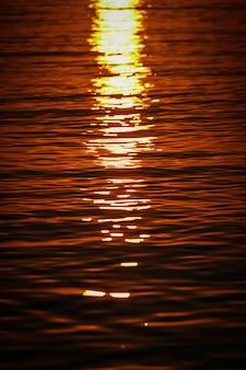 Tiro vertical de las olas del mar que refleja la luz del sol al atardecer