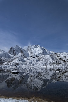 Tiro vertical de un paisaje montañoso nevado que refleja en el lago frío en lofoten, noruega