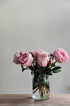 Tiro vertical de peonías rosas con hojas verdes en un florero de vidrio