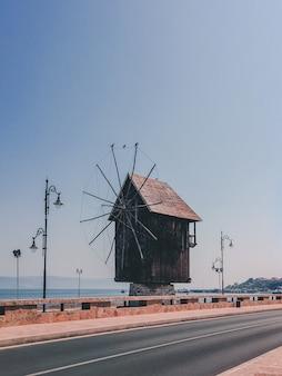Tiro vertical de un pequeño molino de viento de madera al lado de la carretera en el campo