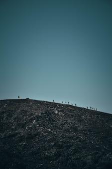 Tiro vertical de personas caminando sobre una empinada colina rocosa en la distancia