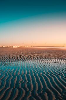 Tiro vertical de la playa con turbinas en el capturado en westenschouwen, países bajos