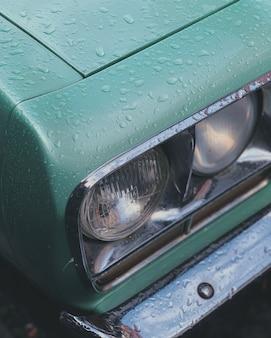 Tiro vertical del primer de los faros de un coche verde