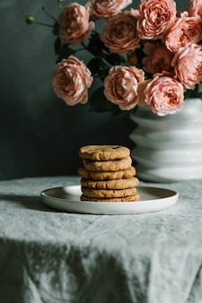 Tiro vertical del primer de galletas cocidas al horno apiladas en una placa cerca de rosas rosadas en un florero en una tabla