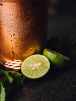 Tiro vertical del primer de limones cerca de una taza de cobre fría con el fondo borroso