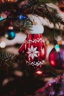 Tiro vertical del primer de un ornamento en forma de guante de navidad que cuelga del árbol