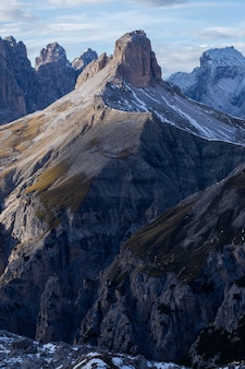 Tiro vertical de las rocas cubiertas de nieve en los alpes italianos