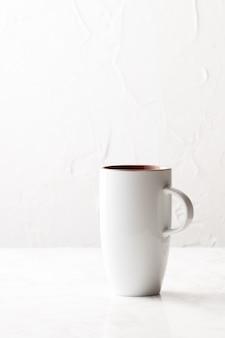 Tiro vertical de una taza de cerámica blanca sobre una superficie blanca