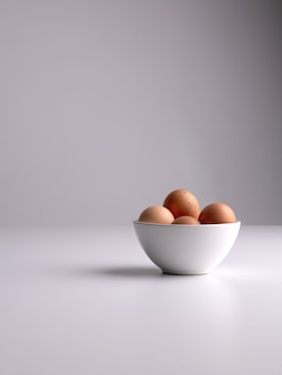 Tiro vertical de un tazón blanco con huevos marrones en una superficie blanca y fondo gris limpio