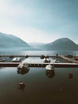 Tiro vertical de veleros en el cuerpo de agua con altas montañas