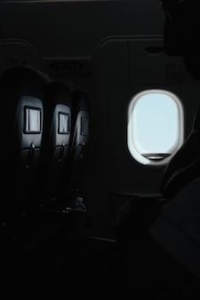 Tiro vertical de la ventana dentro de un avión en el momento del vuelo.