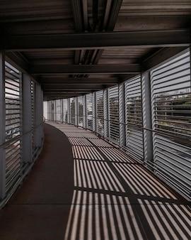 Tiro vertical de ventanas que se reflejan en el piso de un pasillo interior