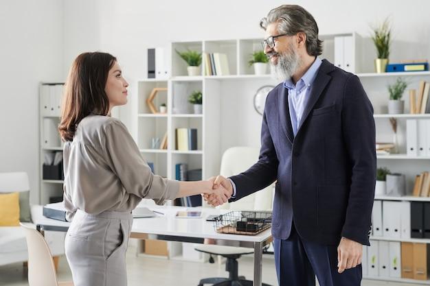 Tiro de vista lateral de mujer joven moderna saludo maduro gerente de recursos humanos con apretón de manos antes de comenzar la entrevista de trabajo