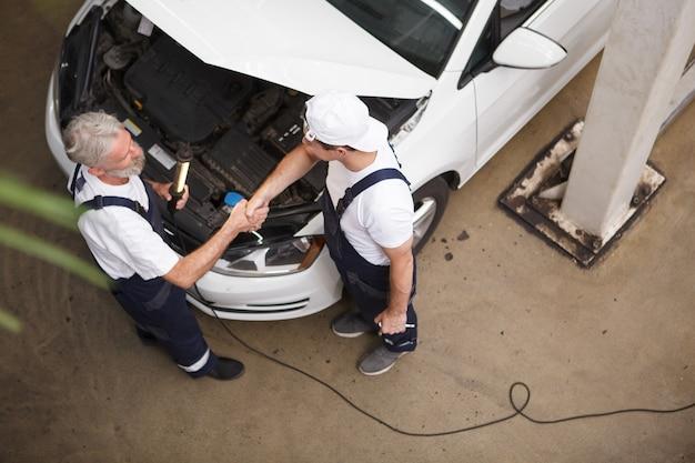 Tiro de vista superior de dos mecánicos de automóviles estrecharme la mano sobre el capó del coche