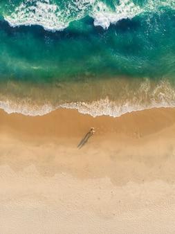 Tiro de vista superior de gente caminando en la playa de varkala