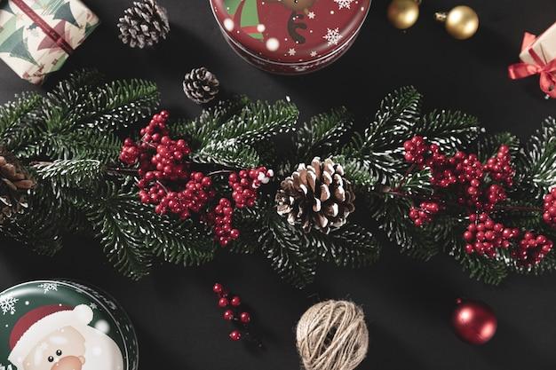 Tiro de vista superior de ramas de pino con cono y regalo en una mesa negra - concepto de navidad
